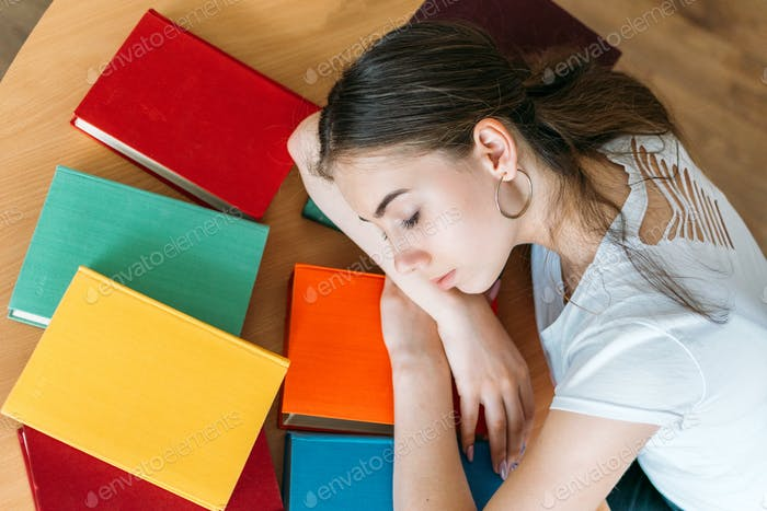 Tired student sleeping on book at library. Top view of female student sleeping at the desk with
