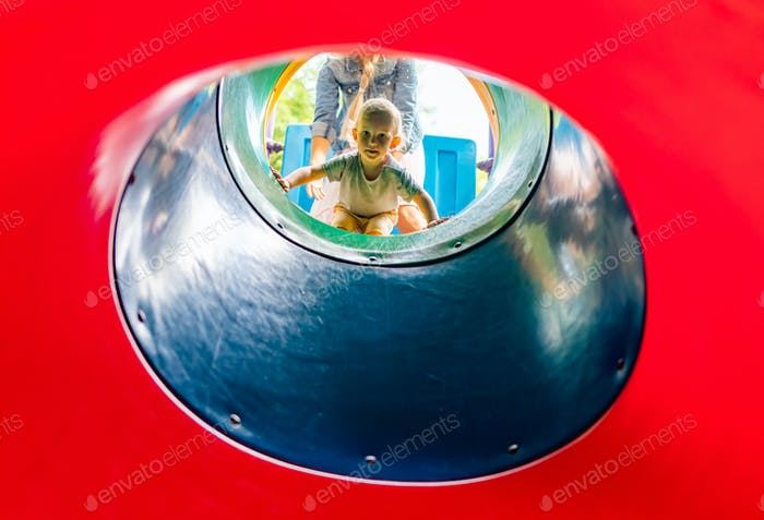 Little child boy playing on slide at park playground