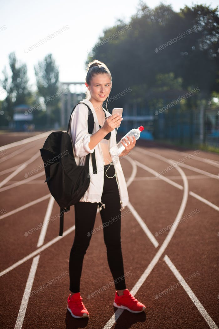 Girl with earphones dreamily looking in camera with cellphone and bottle on racetrack of stadium