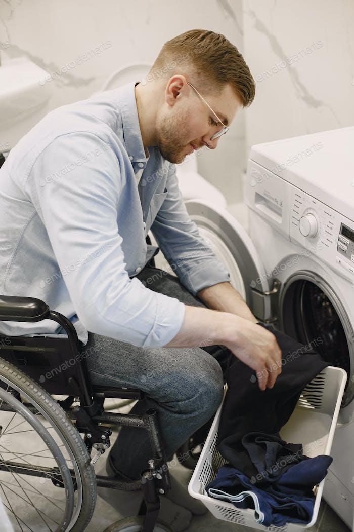 Impaired man in wheelchair put laundry in washing machine