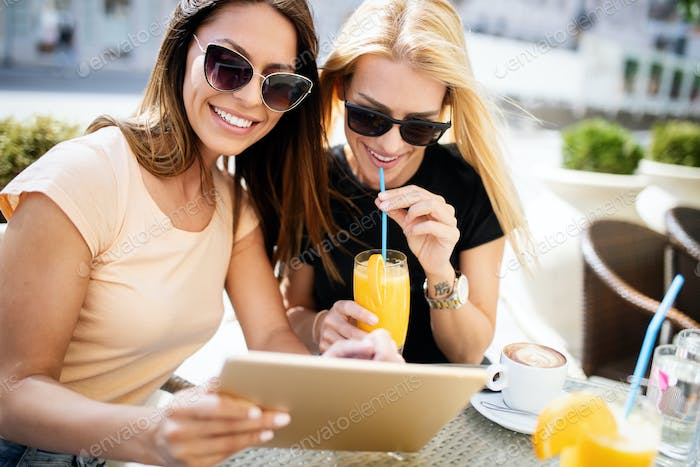 Beautiful girls having fun smiling together in a cafe outdoor