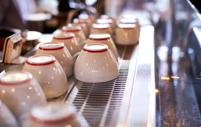 Nahaufnahme von Tassen angeordnet auf Maschine in Coffee Shop