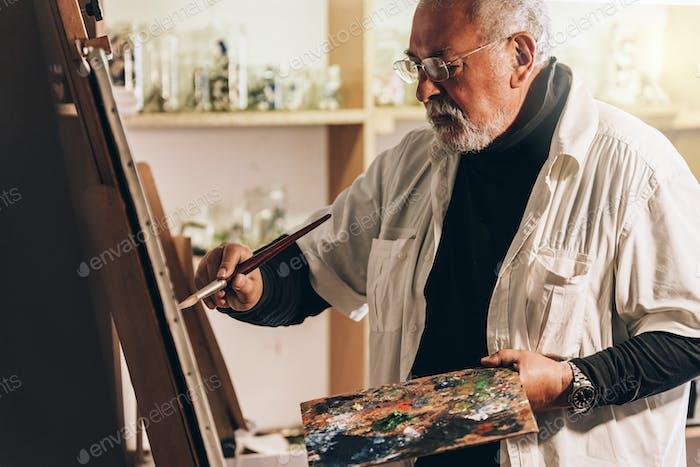 Old man artist painting oils in his studio.