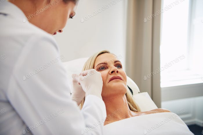 Female doctor doing botox injections on a mature client's face