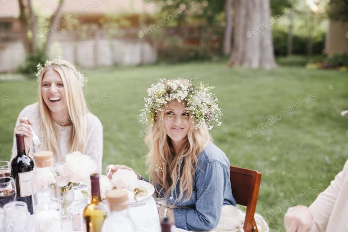 Two smiling women with flower wreaths in their hair, sitting at a table in a garden.
