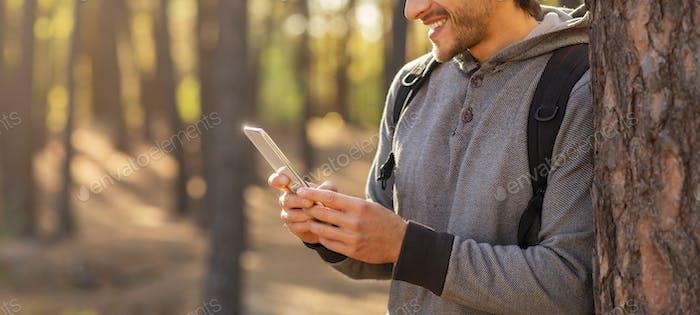 Abgeschnittenes Foto des Menschen mit Smartphone in der Natur