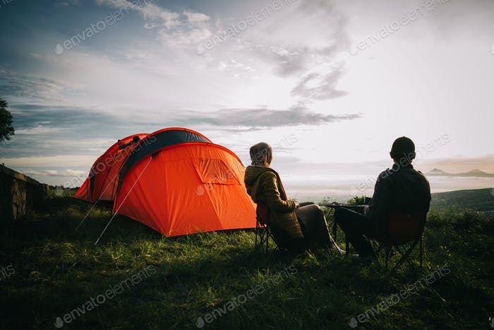 Asian couple camping with sunrise view in mountain