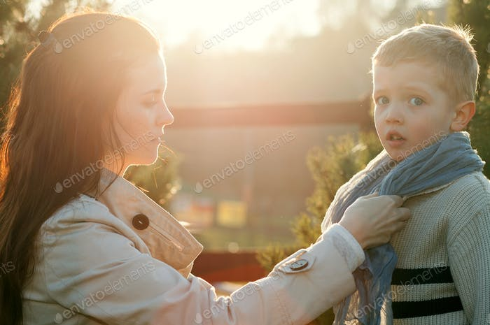 Mother dressing child in scarf
