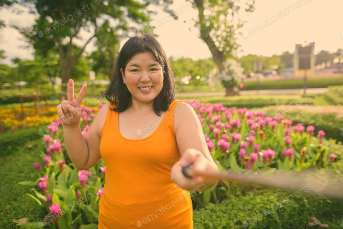 Beautiful overweight Asian woman relaxing at the park in the city of Bangkok, Thailand