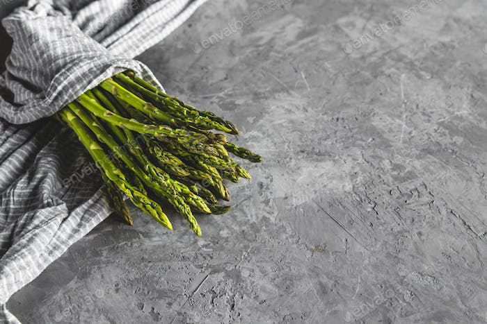 Asparagus in a kitchen towel on a gray background. healthy food