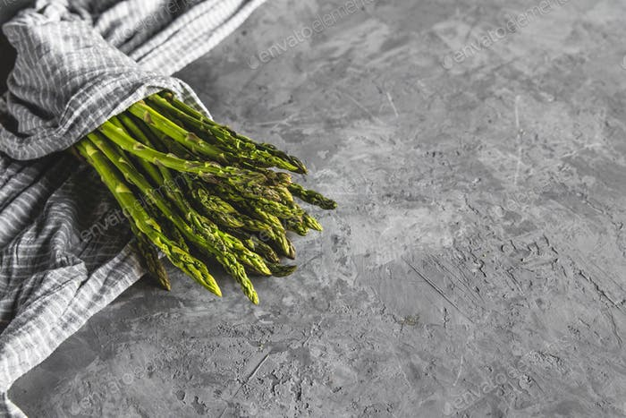 Spargel in einem Küchentuch auf einem grauen Hintergrund. gesundes Essen
