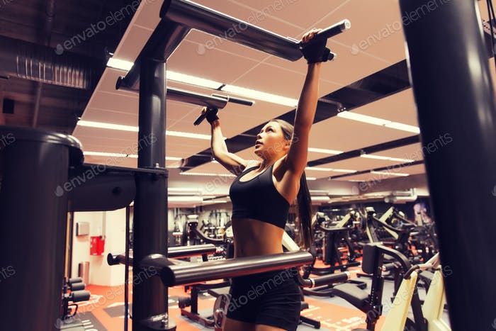 woman exercising and doing pull-ups in gym