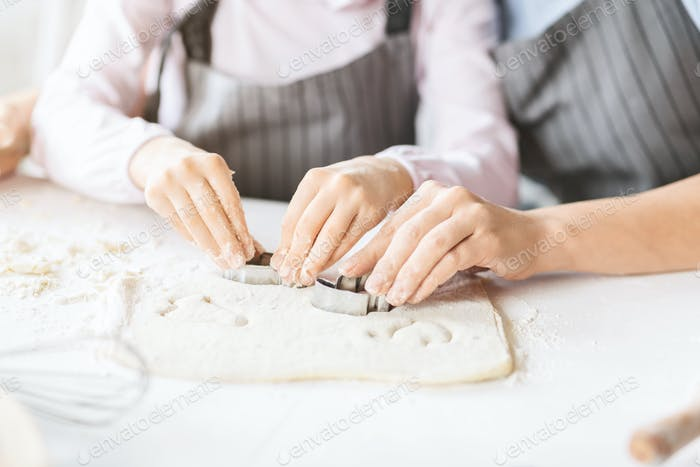 Mother and daughter cutting out different cookie shapes of dough