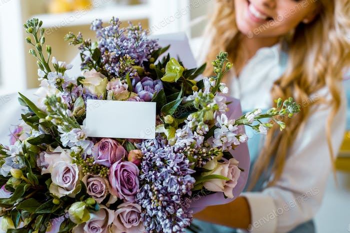 cropped view of woman and flower bouquet with roses, lilac and card with copy space