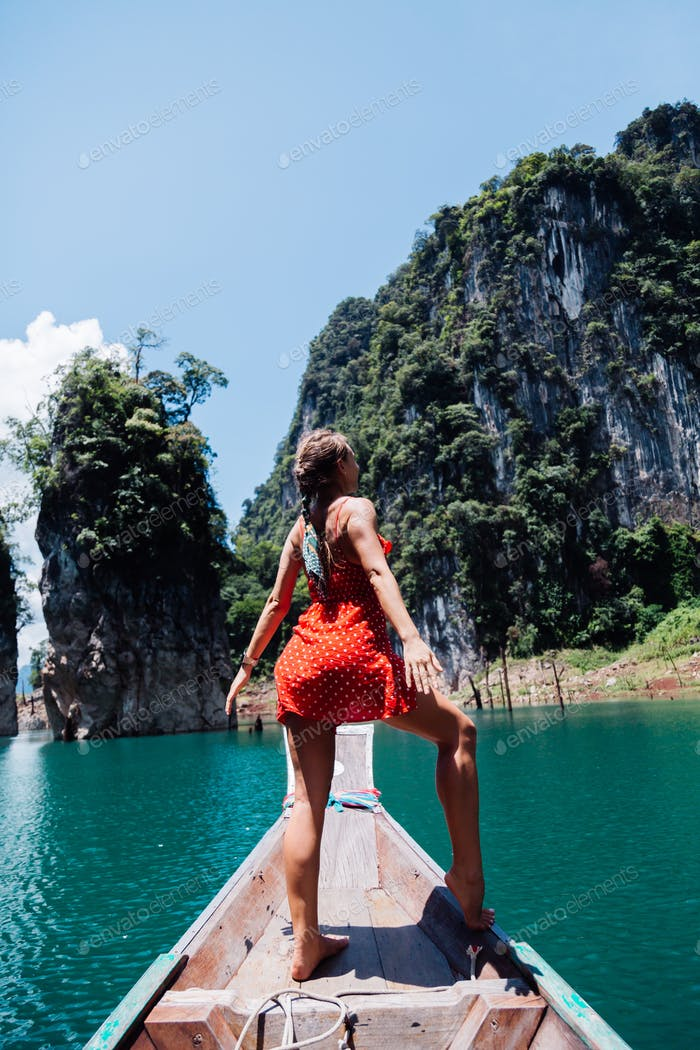 woman tourist in red summer dress on thai asian boat on vacation