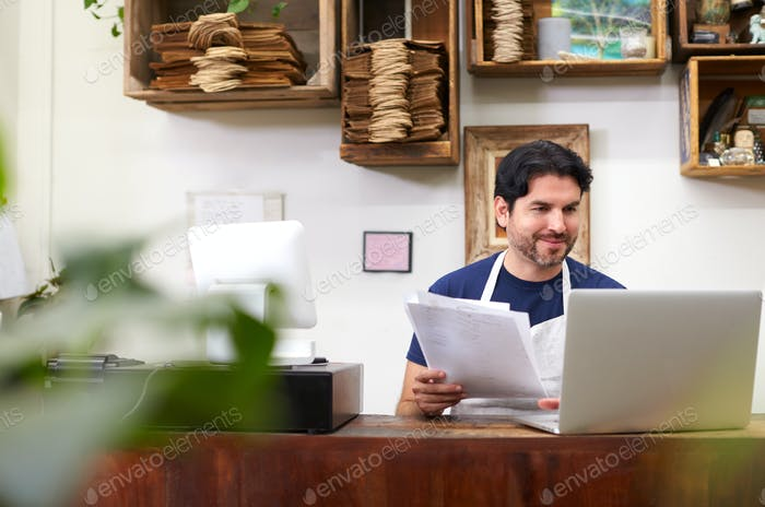Male Assistant Working On Laptop Behind Sales Desk Of Florists Store