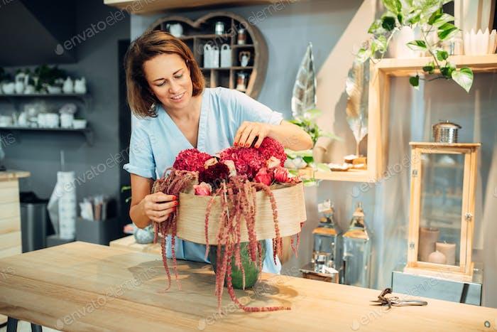 Female florist decorates flowers in shop