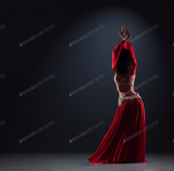beautiful black-haired girl in a red ethnic dress on stage dances oriental dancing with her back
