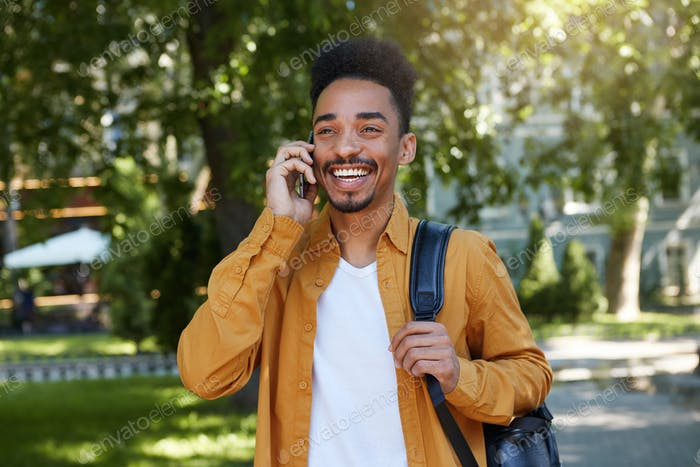 Young African American smiling boy walking after study in the park, talking on the phone