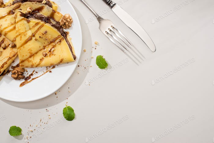 Tasty Crepes With Chocolate Spread And Walnuts on Plate Near Cutlery And Mint Leaves on Background