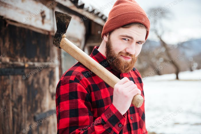 Smiling bearded man holding axe