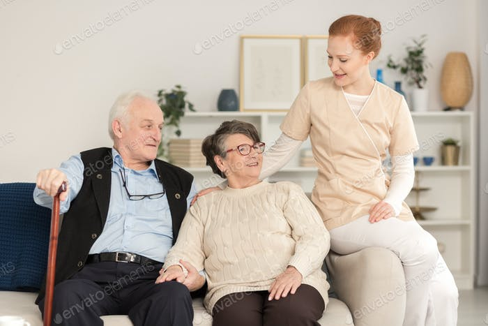 Assistance woman consoling senior couple