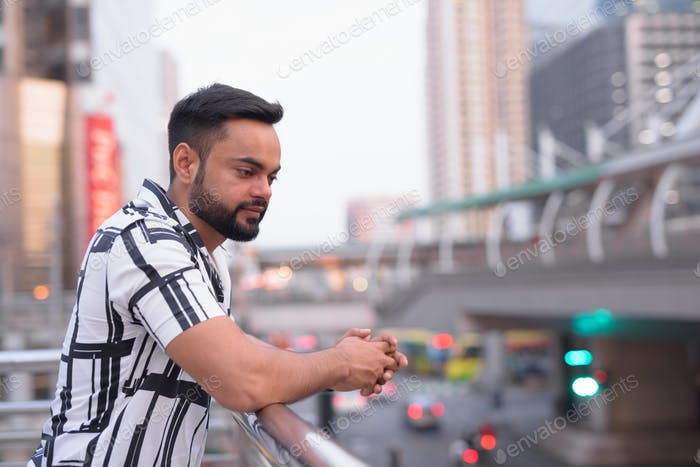 Profile view of young bearded Indian man looking down at view of the city outdoors
