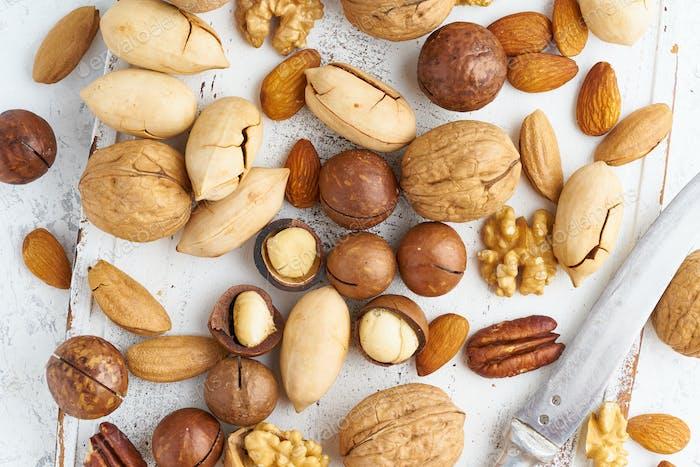 Mix aus Nüssen - Walnuss, Mandeln, Pekannüsse, Macadamia und Messer zum Öffnen der Schale