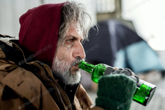 A close-up view of homeless beggar man standing outdoors in city, drinking.