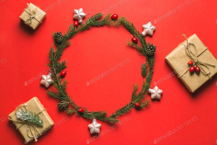Kranz aus Tanne, Tannenzapfen, Vogelbeeren und Geschenkboxen auf rotem Hintergrund. Winter-Design Flach legen