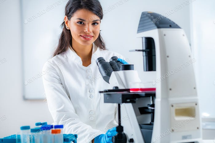 Biology Student Researcher Looking Through the Microscope