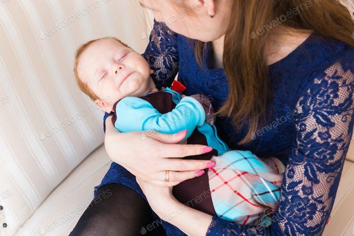 Sweet baby sleeping on hands mother