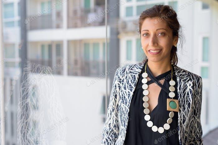 Glückliche hispanische Geschäftsfrau lächelnd am Fenster am Bürogebäude