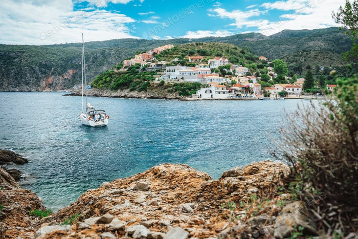 Assos town at Kefalonia. Summer holiday vacation. Sailing boat in the bay on boat trip around Greece