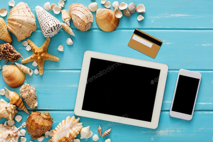 Seashells on blue wood, online shopping on digital tablet