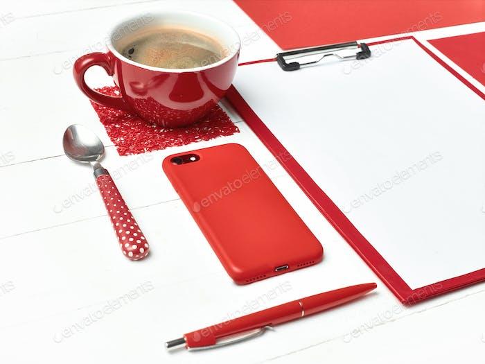 Bürotisch mit buntem Zubehör, weißes Blanko-Notizblock, Tasse, Stift auf weißem Hintergrund.