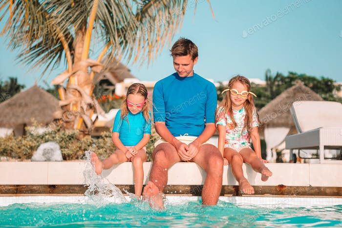 Happy family of four in outdoors swimming pool