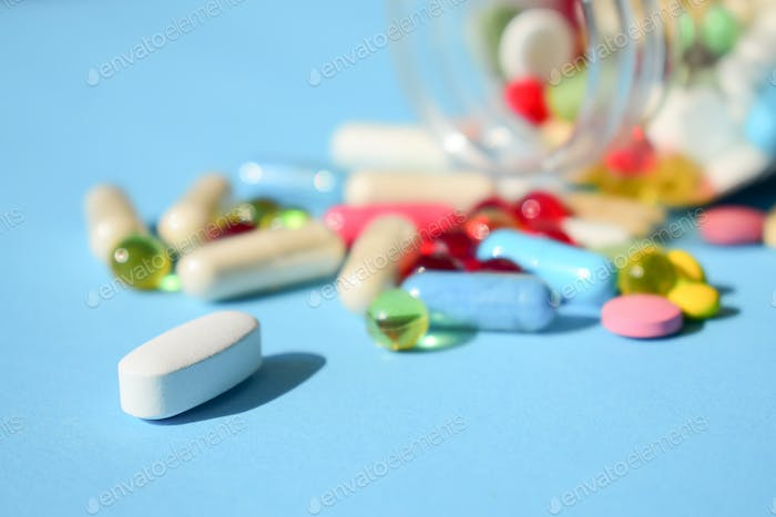Multicolored bright various type pills and capsules spilling out of a toppled white pill bottle