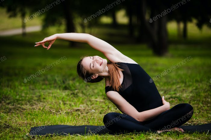 Happy, smiling, young woman resting on the grass at the park after the yoga. She is wearing dark