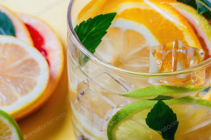 Citrus lemon, lime, orange and grapefruit slices with mint leaves and ice cubes in a glass of water