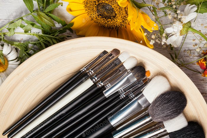 Different type of Make up brushes on a plate next to wild flower