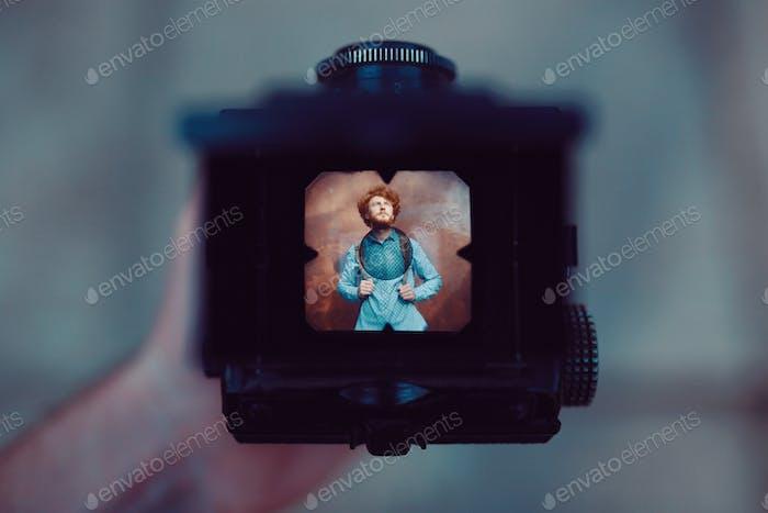 Disparar un retrato de chico guapo con una cámara vintage