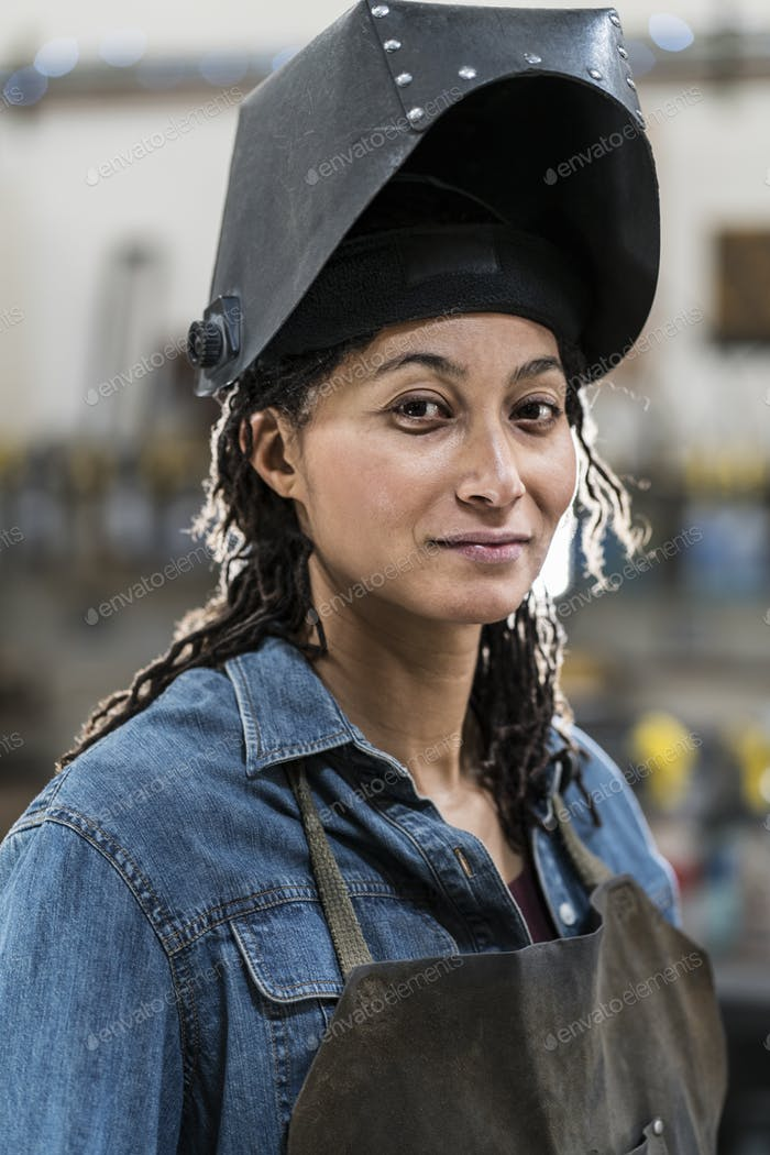 Portrait of woman wearing apron and welding mask standing in metal workshop, smiling at camera.