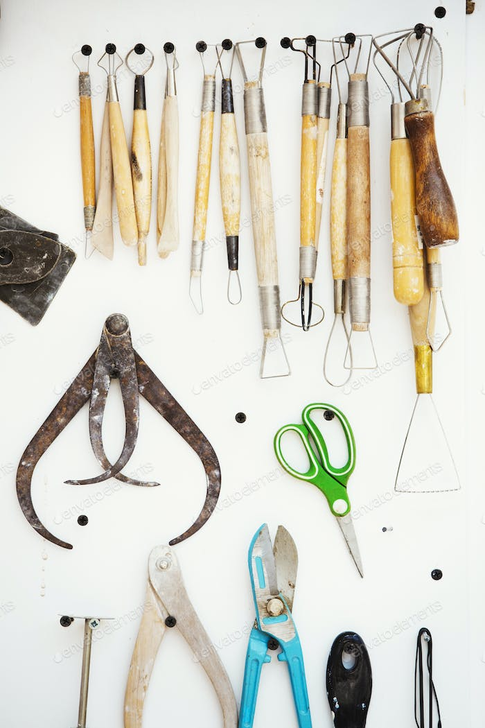 A tool board, with brushes, hand tools and pliers and curved shaing tools, calipers hanging on the