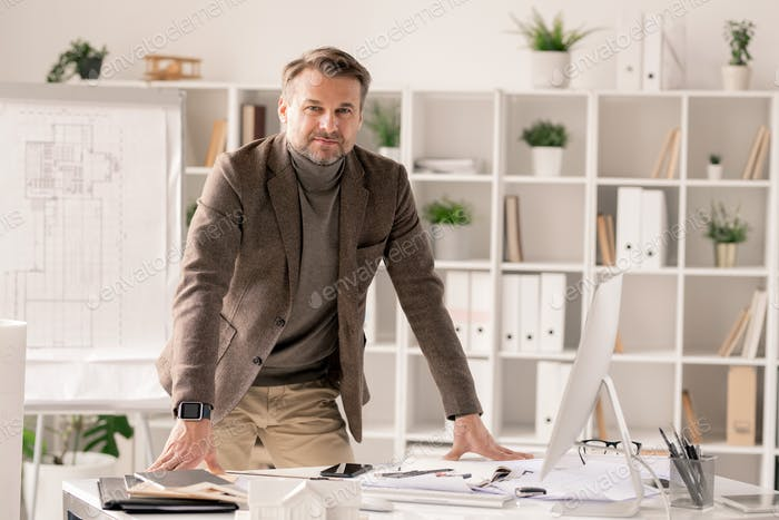 Successful and confident architect in formalwear bending over desk in office