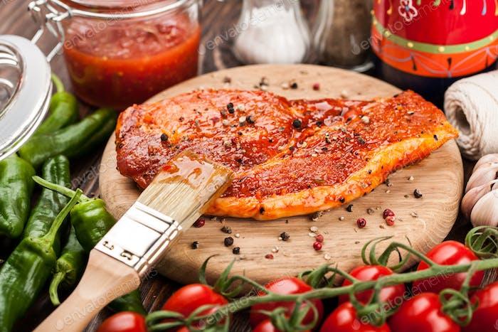 Marinated raw pork steaks on cutting board