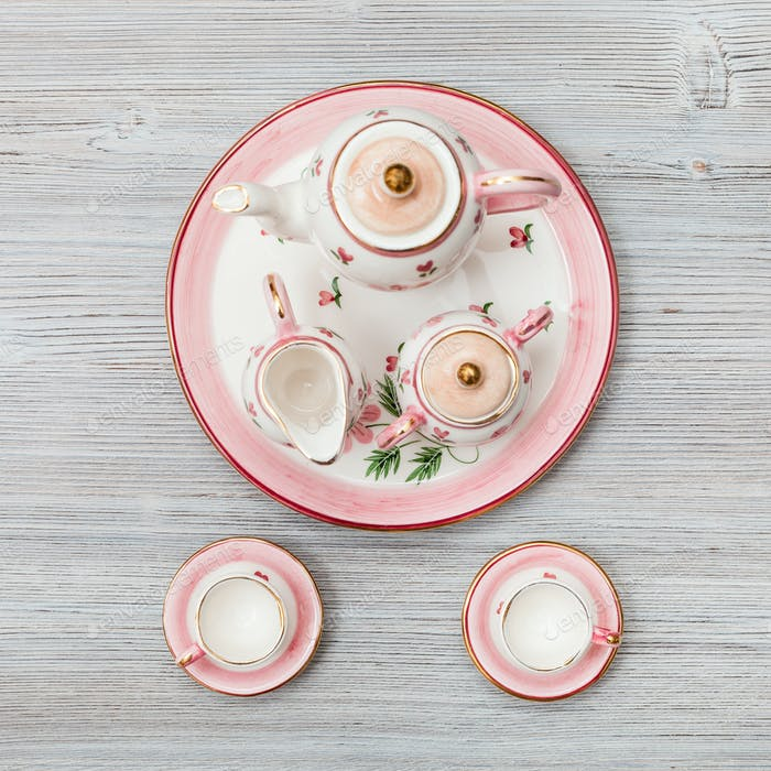 pink porcelain tea set on gray brown plank