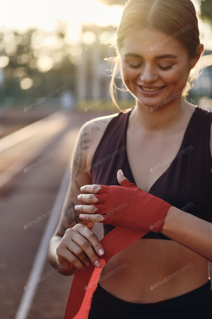 Sporty smiling girl in sportswear joyfully wrapping red boxing bandage on hand on city stadium