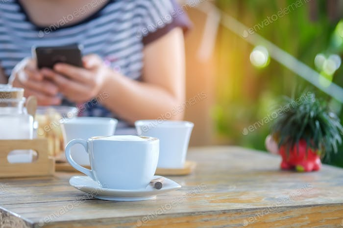 Coffee white mug on wooden table with people are playing smart p
