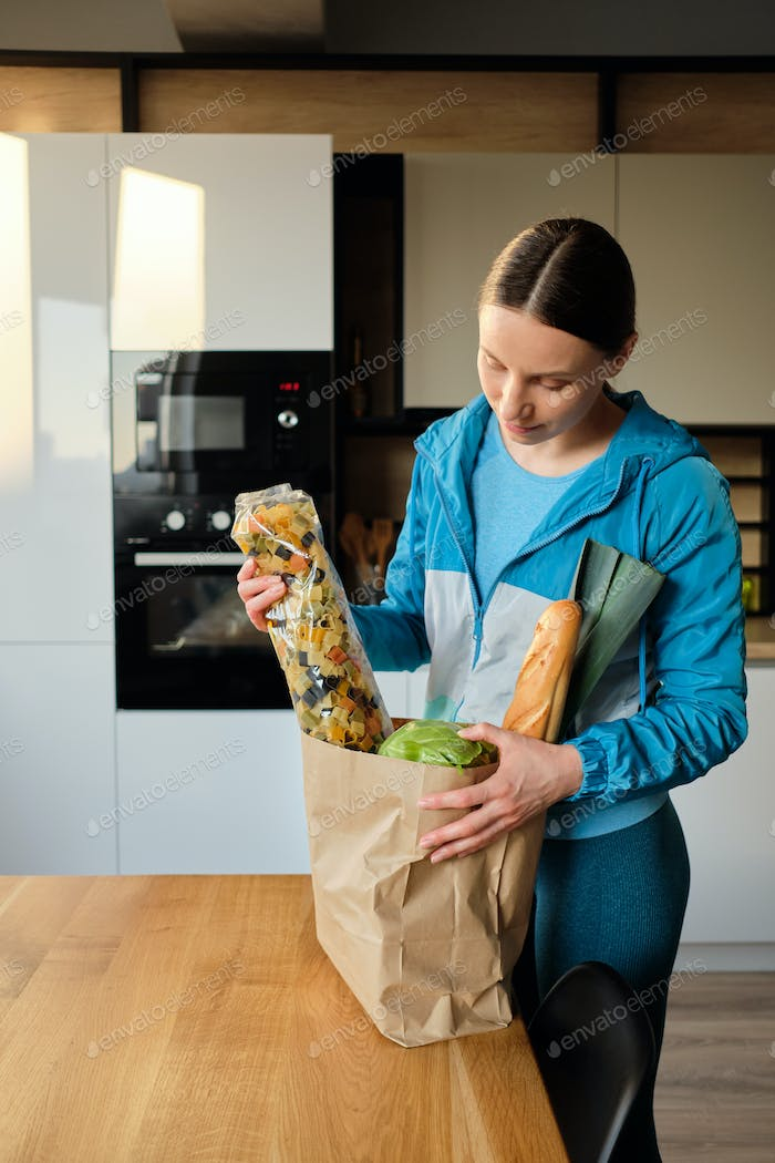 Young woman reads the composition of pasta on the bag